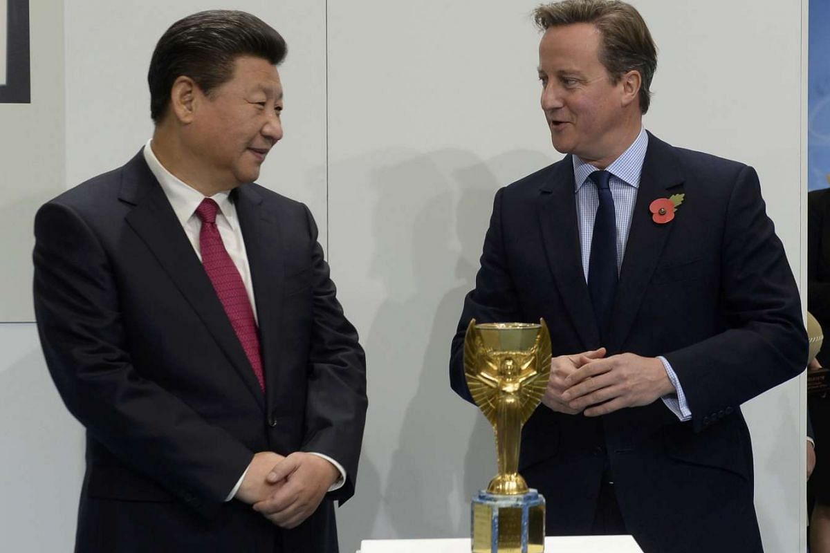 Britain's Prime Minister David Cameron and China's President Xi Jinping (left) view the Jules Rimet trophy during a visit to the City Football Academy in Manchester on Oct 23, 2015.