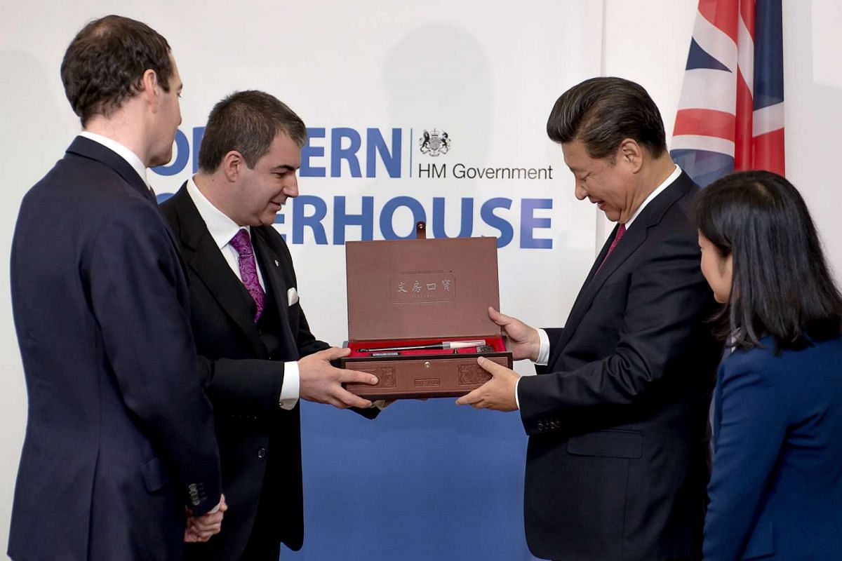 Chinese President Xi Jinping (right) presents a gift of paint brushes to Professor Kostya Novaselov (second from left) as Chancellor of the Exchequer George Osborne (left) looks on, during Mr Xi's visit to Britain's National Graphene Institute at the