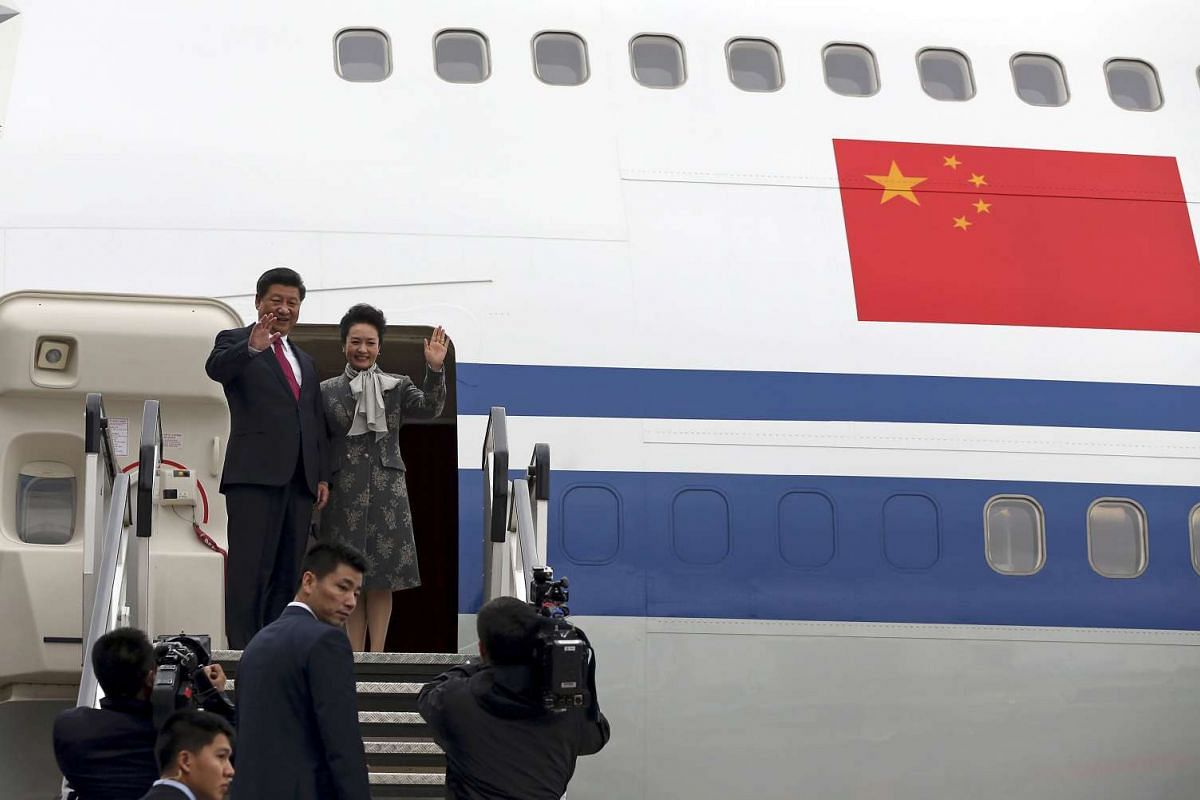 China's President Xi Jinping and his wife Peng Liyuan wave as they board their aircraft to return to China, at Manchester airport, on Oct 23, 2015.