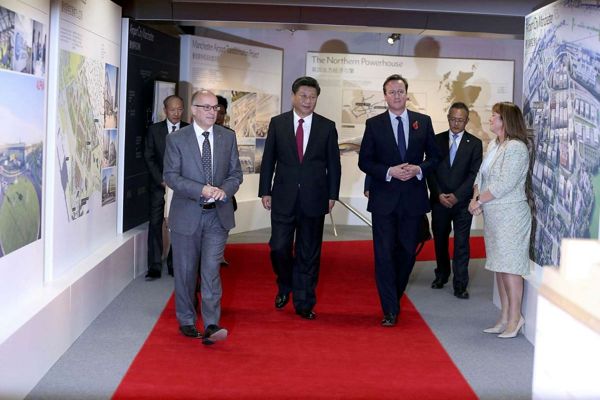 China's President Xi Jinping (centre) walks with Prime Minister David Cameron (right) and Manchester Airport chief executive Charlie Cornish, as they tour an exhibition of future developments in the north of England on Oct 23, 2015.