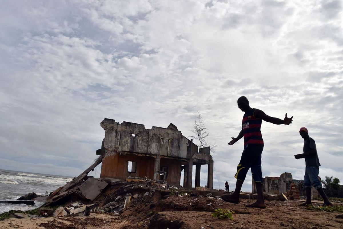 A man gestures near the ruins of the former sub-prefecture of the Ivorian town of Grand Lahou, situated where the Bandama River meets the Gulf of Guinea, on Oct 15, 2015. Grand Lahou is in danger of sinking under waves by a combination of climate cha