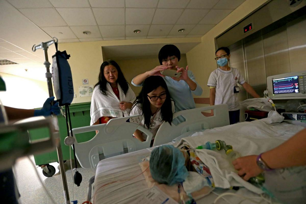 Jeremy's mother, Maggie Yu (centre), looking at her child as he was wheeled out from the operating theatre. With her are her mother-in-law Yang Keqin, 59, and her sister Yu Da Yan, 35. Da Yan came to Singapore a few days before the surgery to help th