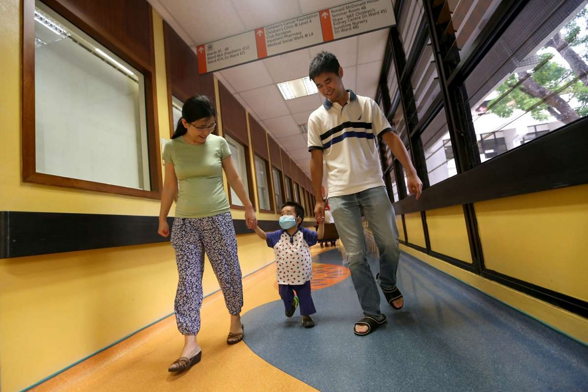Jeremy walking with his parents, Guo Yang and Maggie Yu, as they leave the National Univeristy Hospital on Aug 25, 2015 - 45 days after the transplant. He has to wear a face mask to avoid catching infections.