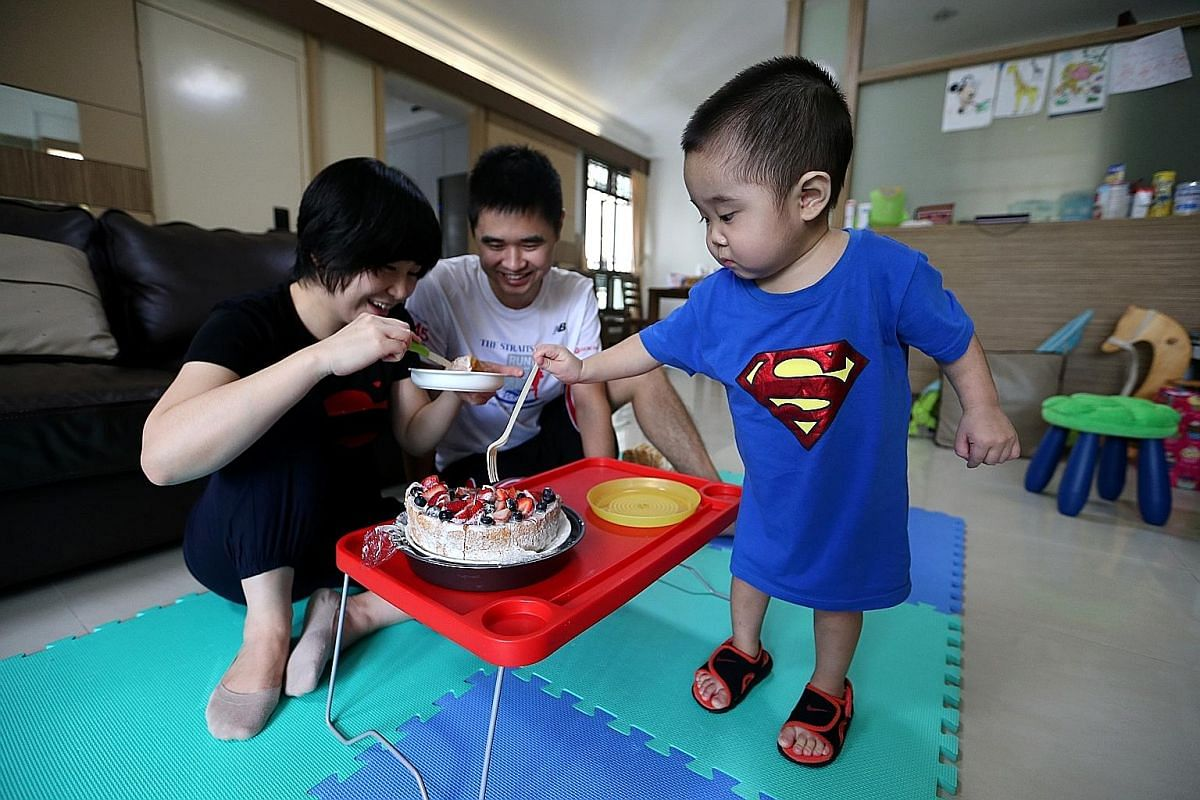Jeremy picking at the fruits on his birthday cake when his parents are not looking as the family celebrates his second birthday on Sept 29. Both father and son are recovering well after the transplant operation. Mr Guo is back to playing basketball a