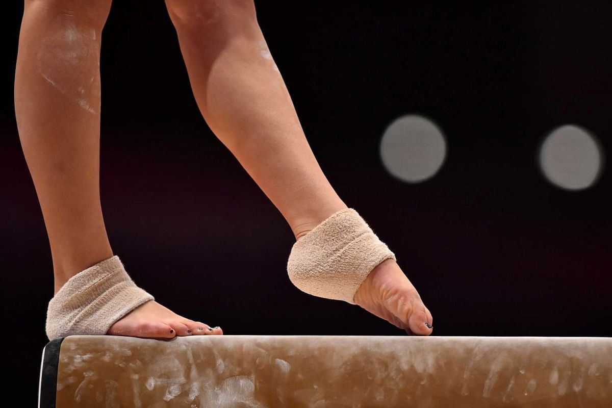 A gymnast competing on the beam during the first day of the 2015 World Gymnastics Championship.