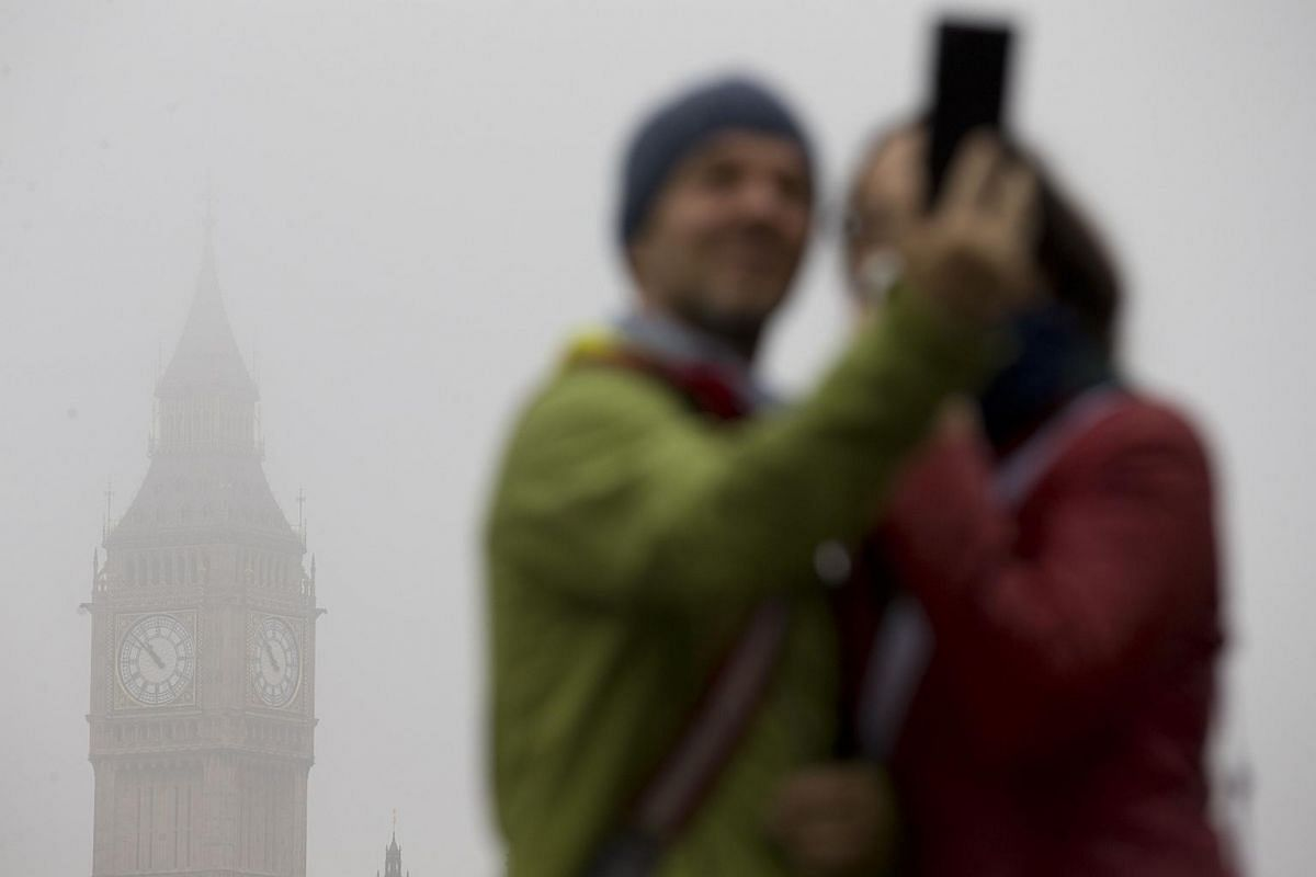 A couple taking a selfie in front of the fog-shrouded Houses of Parliament in central London.