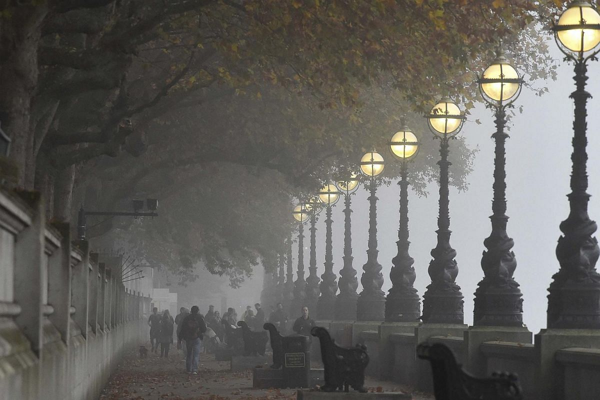 Workers walking along the River Thames on a misty morning in London, Britain.