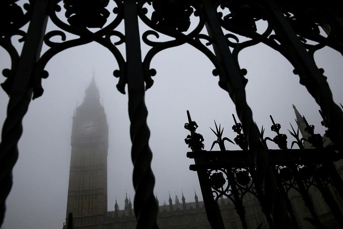 The Big Ben Clock Tower seen through a gate during a foggy day in central London.