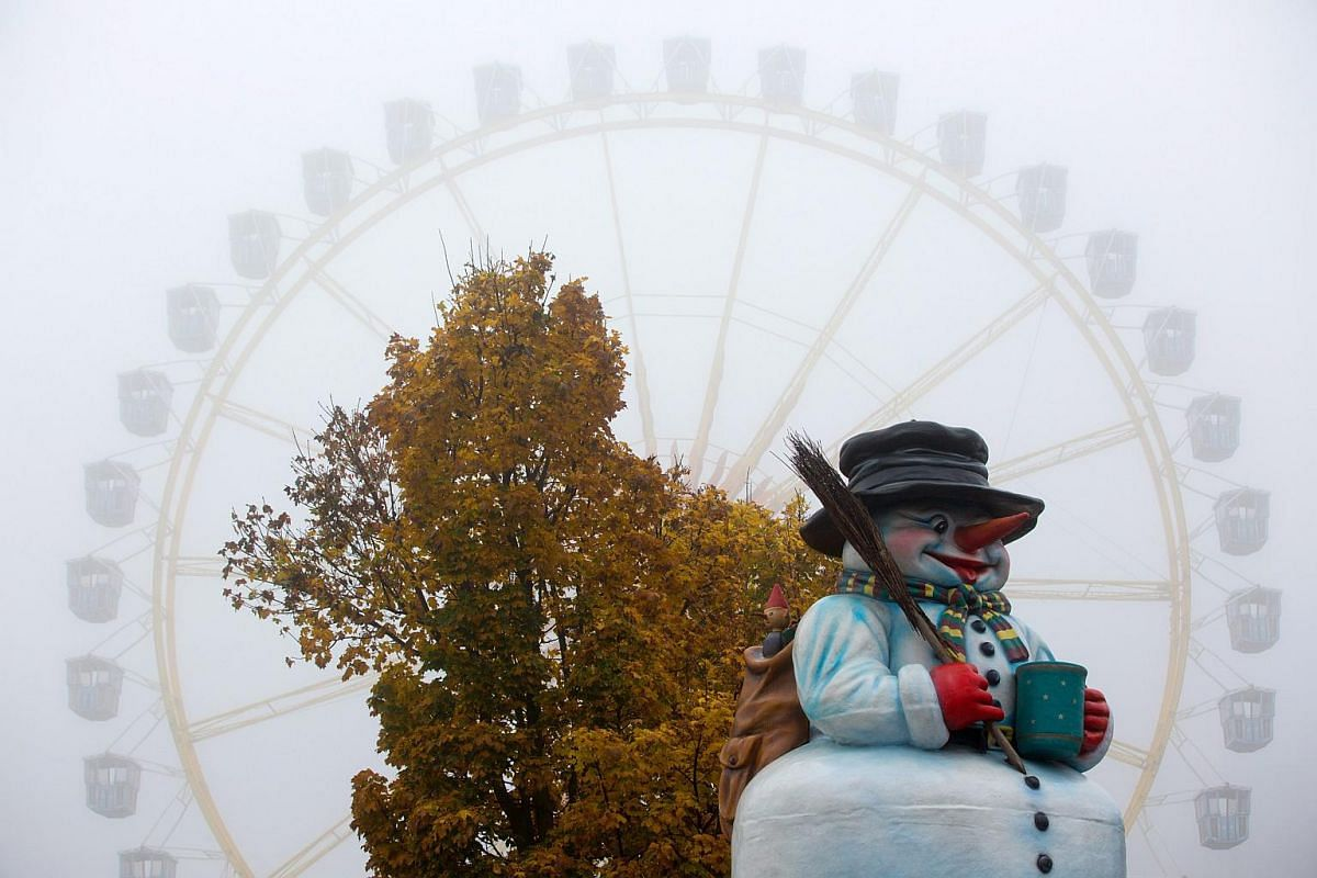 A view of a plastic snowman and a ferris wheel shrouded in heavy fog in Hamburg, Germany.