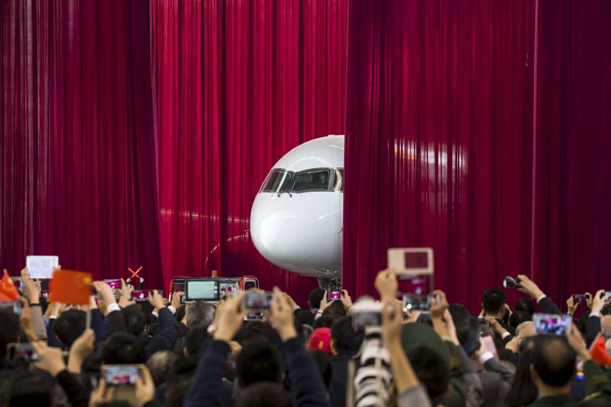 People take pictures as the first C919 passenger jet made by the Commercial Aircraft Corp of China (Comac) is pulled out from behind a curtain during a news conference at the company's factory in Shanghai, on Nov 2, 2015.