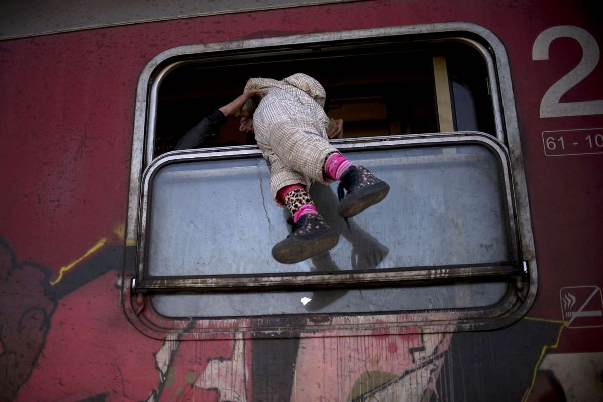 A man carries a child through a train's window as migrants and refugees board a train heading to Serbia after crossing the Greek-Macedonian border in Gevgelija on nOV 4, 2015.