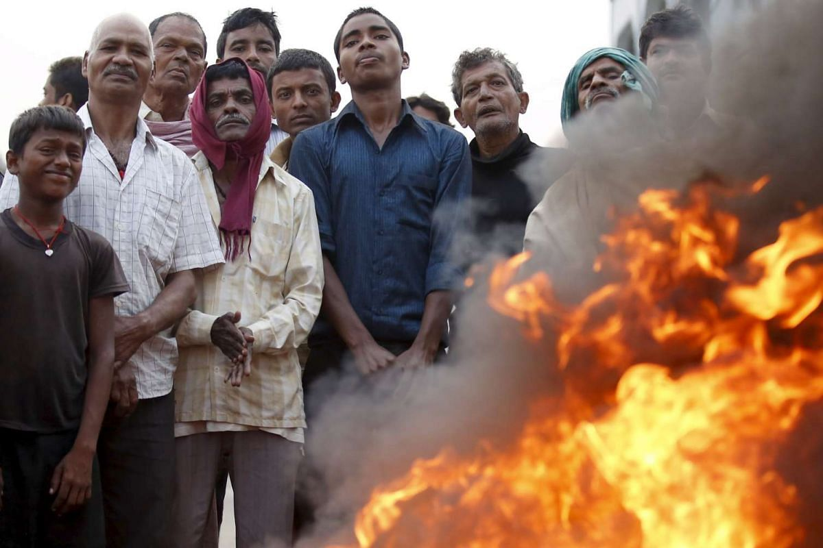 Protesters stand near a burning tyre to block the highway connecting Nepal to India during a general strike in Birgunj, Nepal, on Nov 5, 2015.