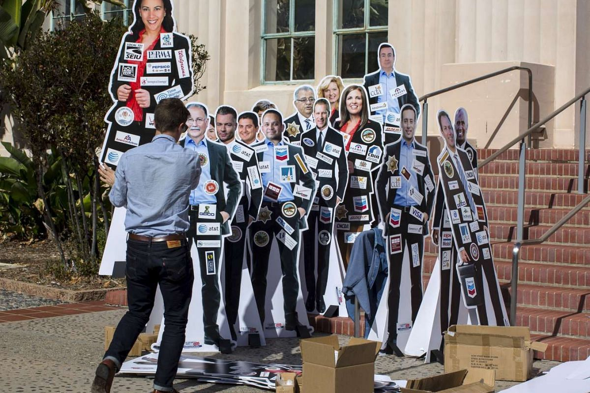 Backers of a proposed initiative in California create a display of their concept - requiring lawmakers to display on their clothing their top 10 campaign contributors - at a news conference in San Diego, California, on Nov 4, 2015.