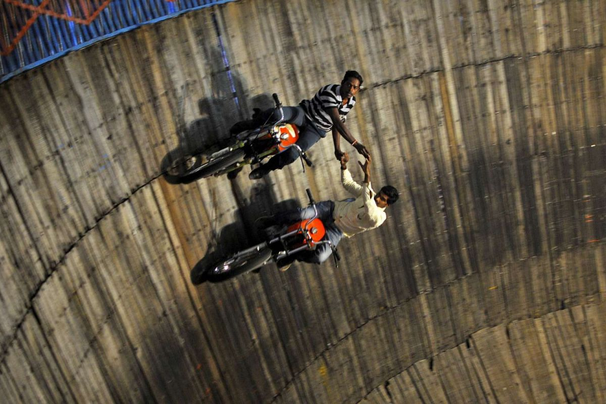"Stunt performers ride their motorcycles on the walls of the ""Well of Death"", at a fair on the outskirts of Bengaluru, India."