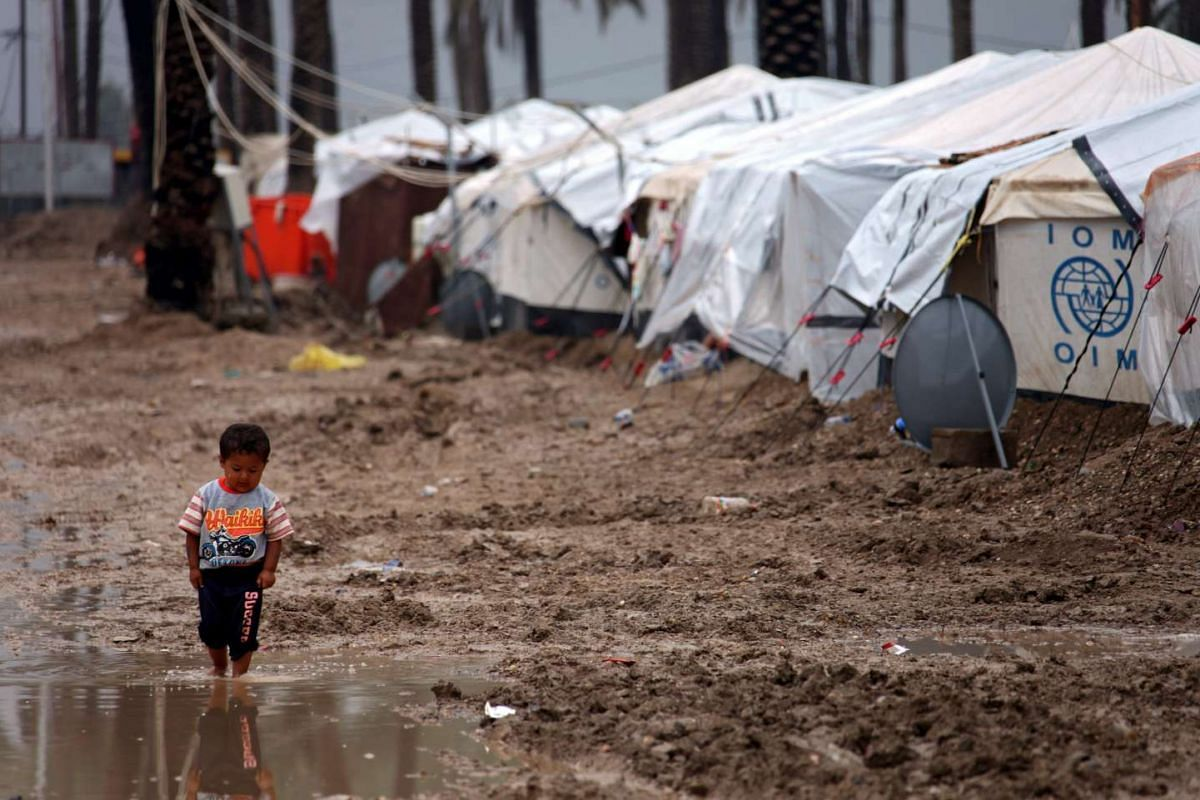 An Iraqi displaced child, who was forced to flee his home in Ramadi city western Iraq, walks amid mud during a rainy day at a refugee camp in southern Baghdad, Iraq