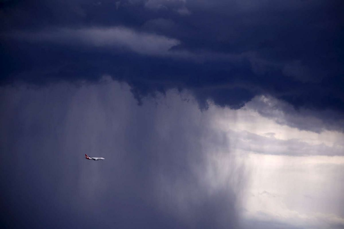 A Qantas Boeing 737-800 plane flies through heavy rain as a storm moves towards the city of Sydney, Australia.