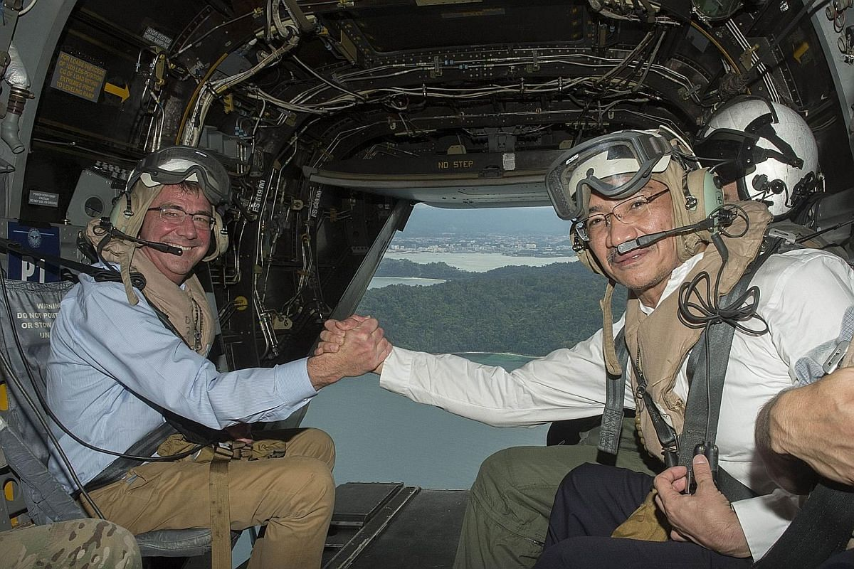 United States Secretary of Defence Ashton Carter (left) and Malaysian Defence Minister Hishammuddin Hussein aboard a V-22 Osprey aircraft on Thursday while on their way to the aircraft carrier USS Theodore Roosevelt, which was passing through the Sou