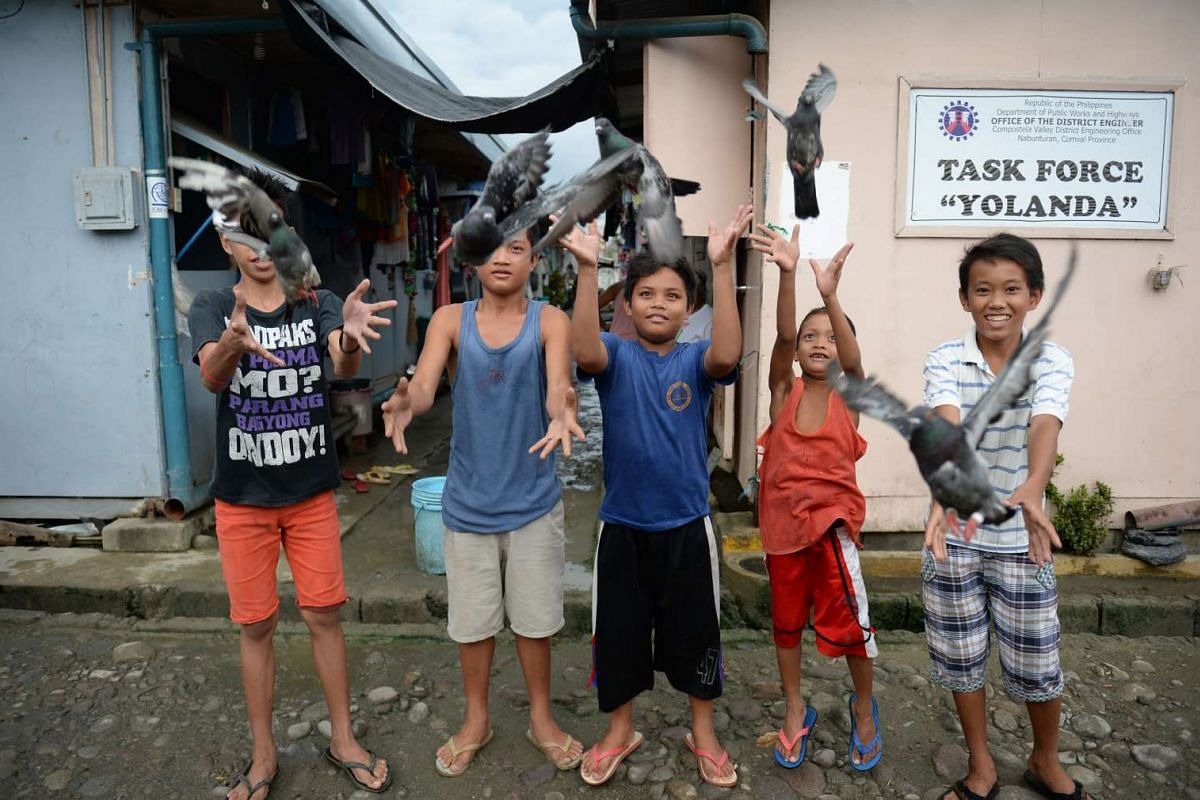 """This photo taken on Nov 1, 2015 shows young boys releasing their pet pigeons at a temporary shelter site locally dubbed """"bunkhouses"""" for survivors of typhoon Haiyan in Tacloban City, Leyte province, central Philippines. Two years after the super typh"""