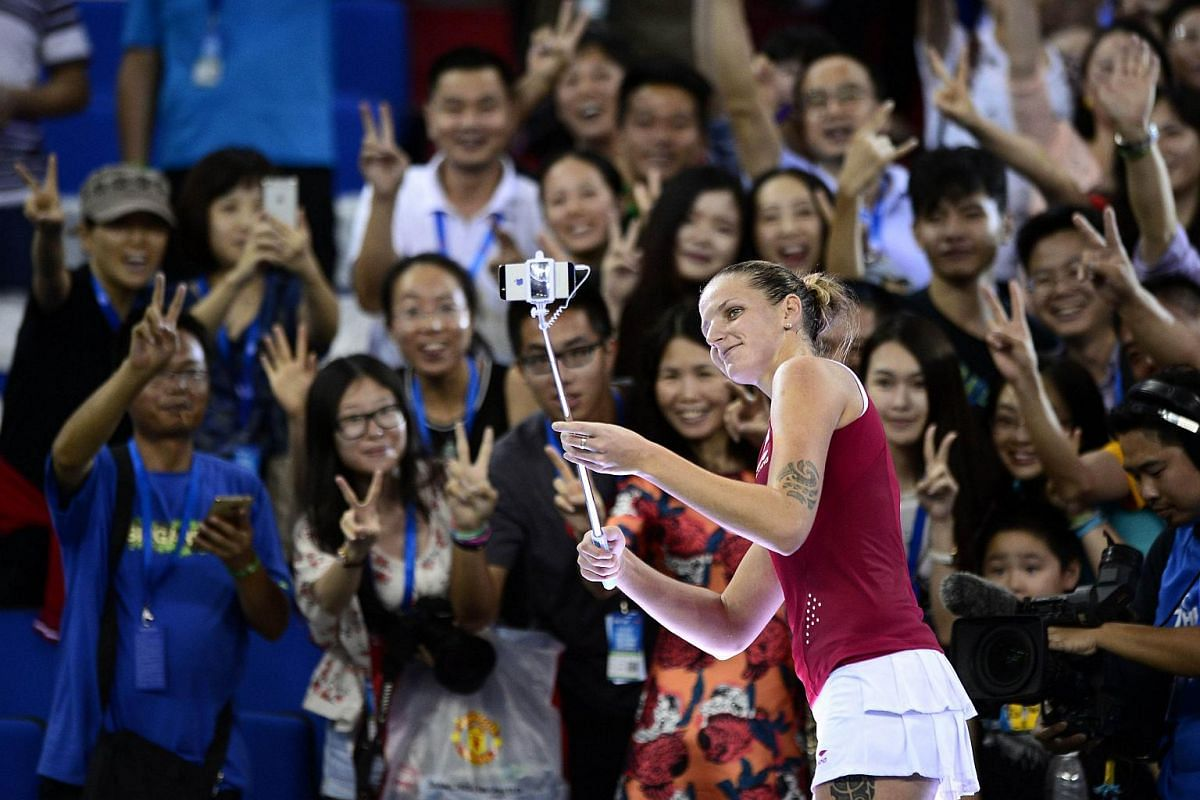 Karolina Pliskova of the Czech Republic using a selfie stick to take a photo with fans after winning the women's singles semi-final match against Elina Svitolina of Ukraine at the WTA Elite Trophy in Zhuhai, southern China's Guangdong province, on No