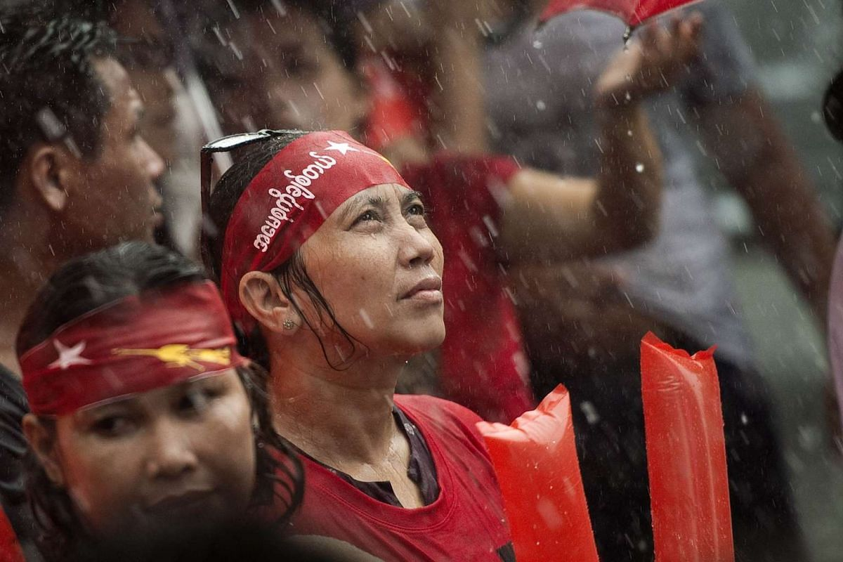 Supporters of Myanmar opposition leader Aung San Suu Kyi braving the rain as they hear the first official results outside the National League of Democracy headquarters in Yangon on Nov 9, 2015.