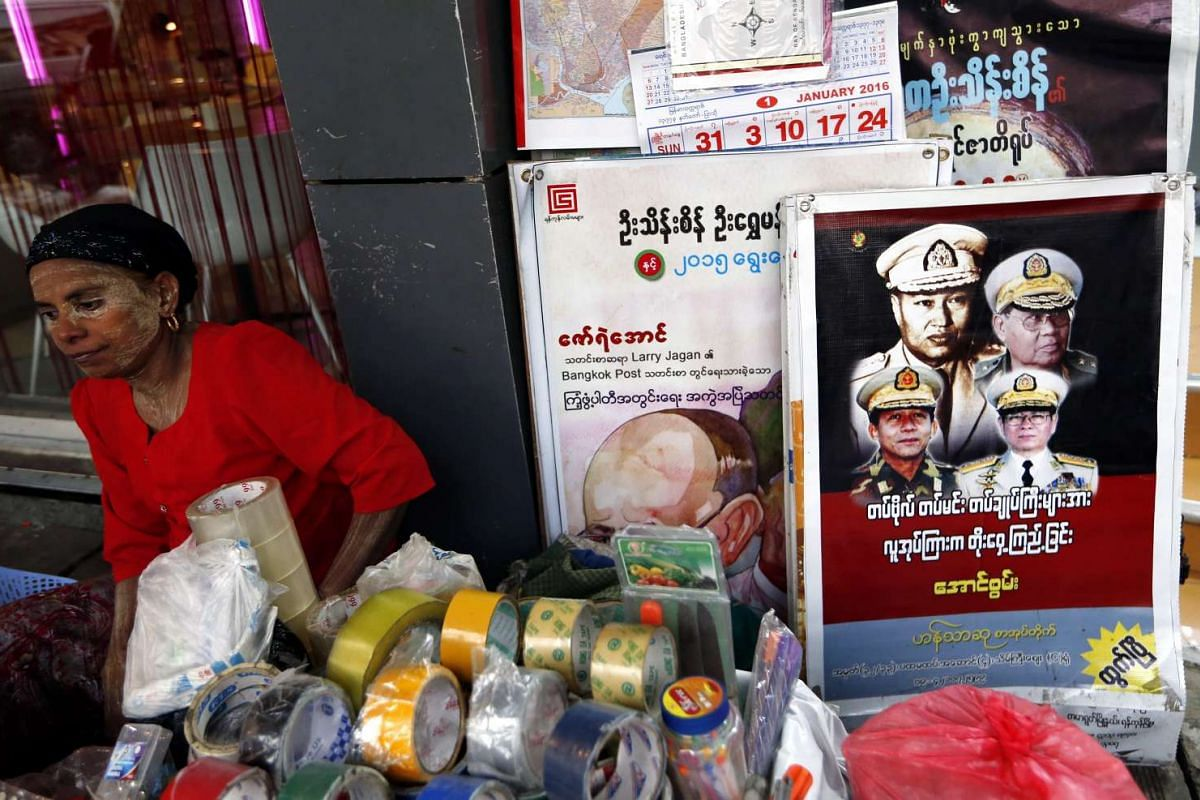 A Myanmar vendor sitting next to a poster showing former Myanmar leader Than Shwe (top right) and other ex-junta leaders at a roadside stall in Yangon, Myanmar, on Nov 9, 2015.