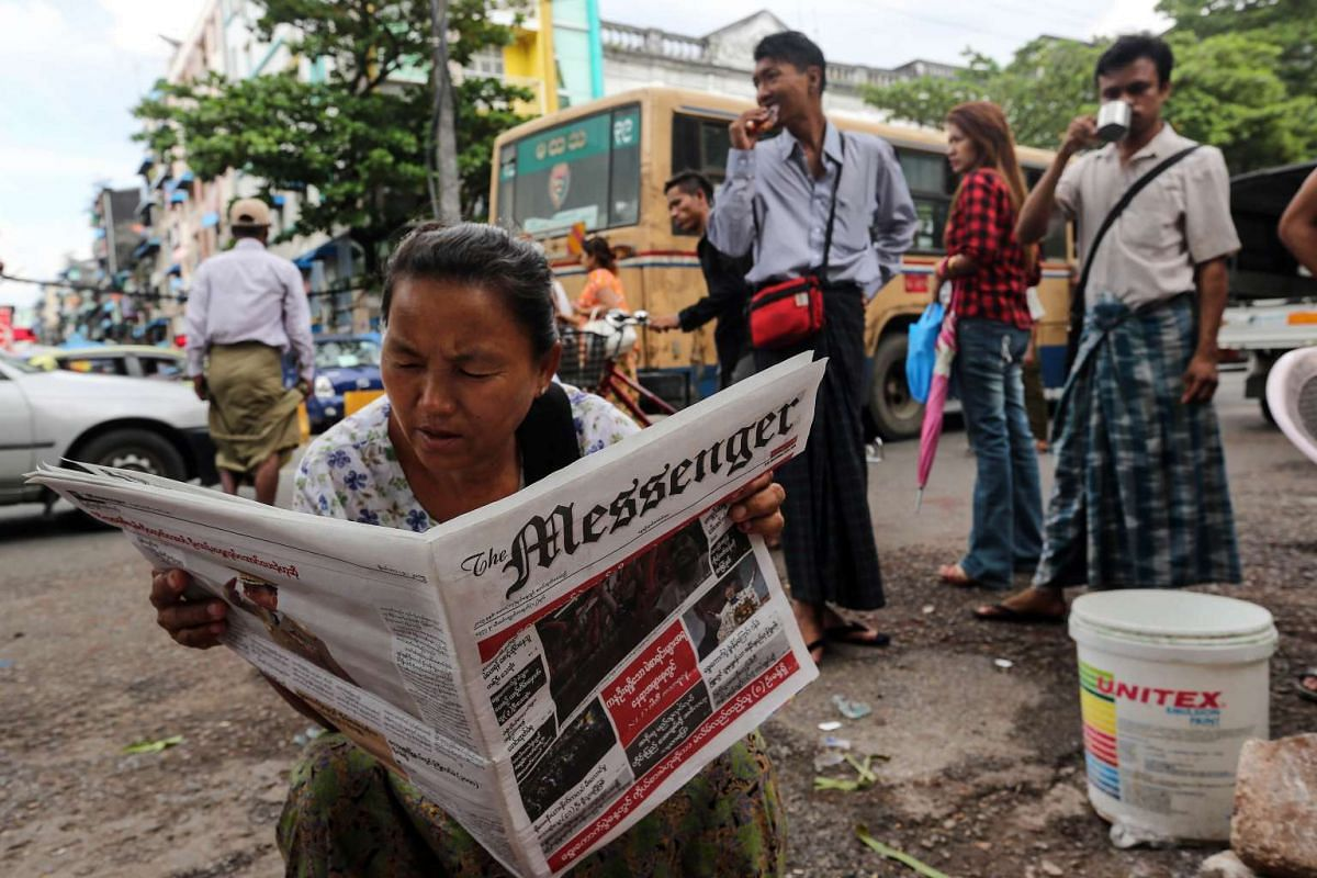 A woman reading a newspaper at a bus station in Yangon, Myanmar, on Monday, Nov 9, 2015.