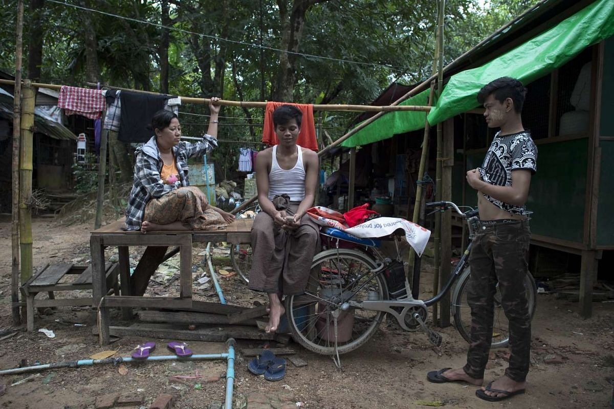 A supporter (centre) of Myanmar opposition leader Aung San Suu Kyi checking his mobile phone outside his shack in front of the National League of Democracy headquarters in Yangon on Nov 10, 2015.