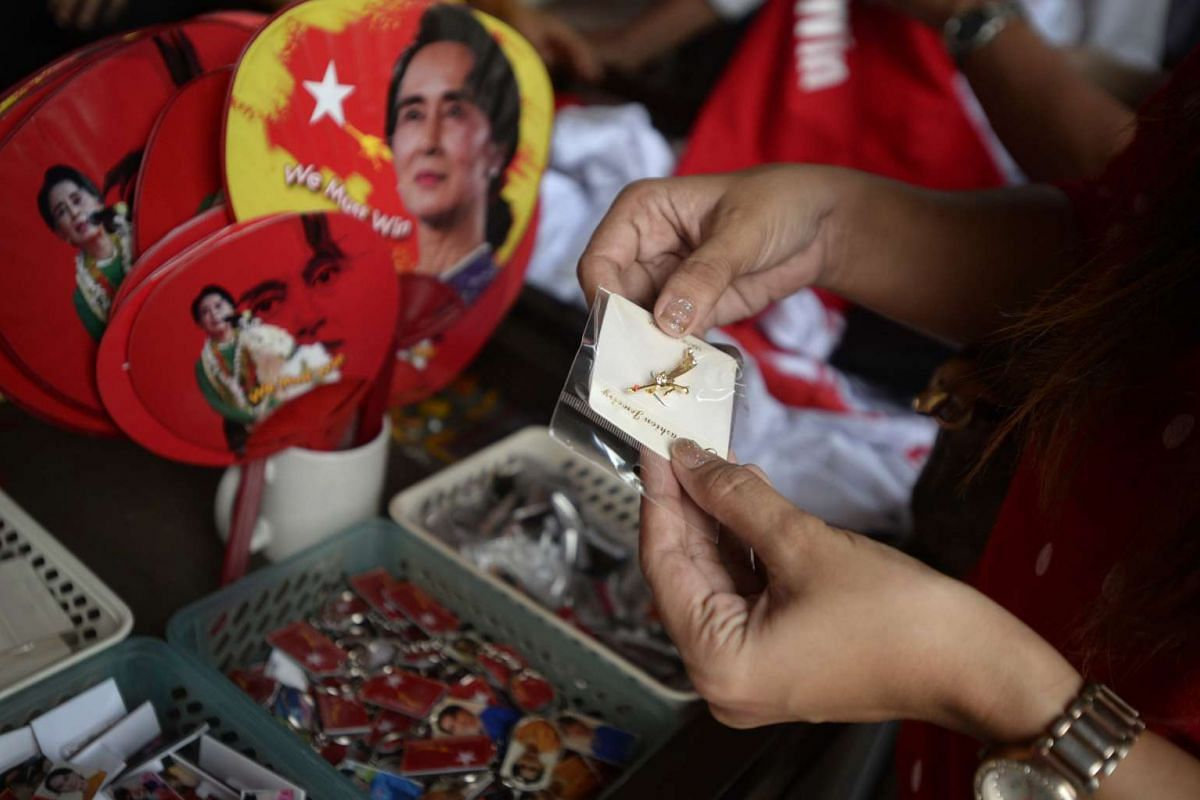 A woman picking out a brooch in the shape of a peacock, the symbol of the National League for Democracy, at a souvenir shop outside the headquarters in Yangon, Myanmar, on Nov 10, 2015.