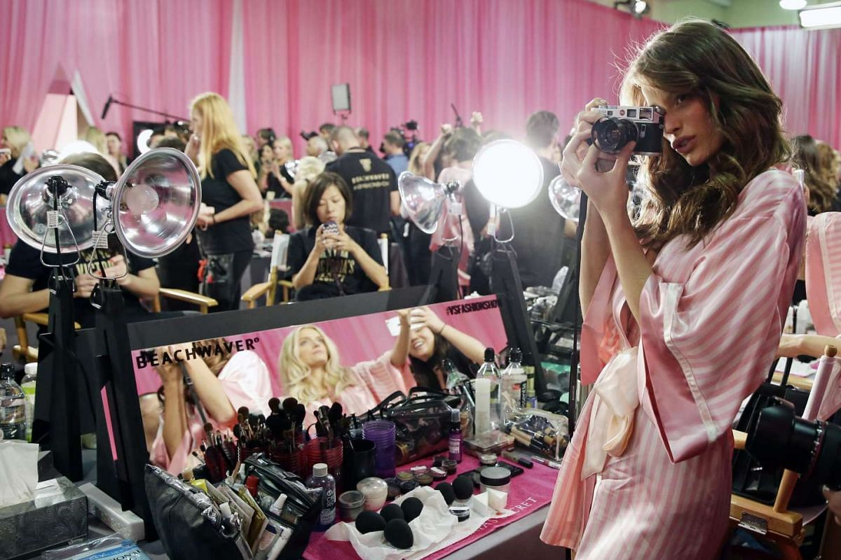 Brazilian Victoria's Secret model Flavia Lucini taking pictures of other models with her Leica M6 camera backstage during hair and make-up before the start of the 2015 Victoria's Secret fashion show at the Lexington Armory in New York on Nov 10, 2015