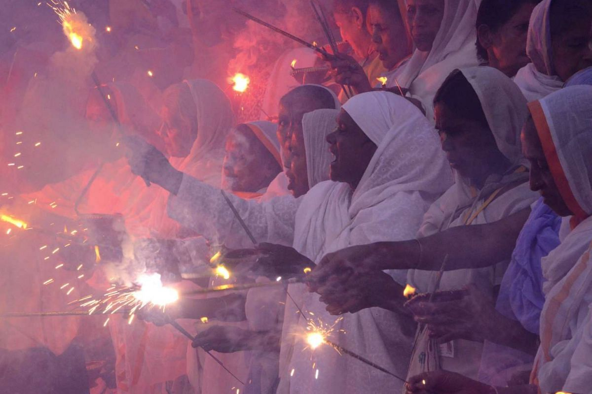 Widows abandoned by their families lighting sparklers after offering prayers on the banks of the river Yamuna as part of Deepavali celebrations organised by non-governmental organisation Sulabh International in Vrindavan in the northern Indian state