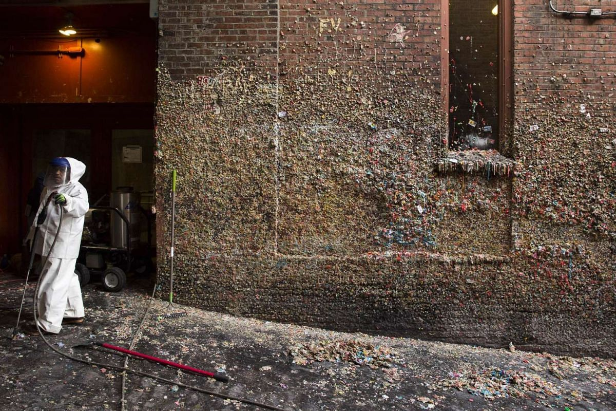 A worker is pictured holding a pressure washer as 20-years worth of chewing gum is removed from Post Alley at Pike Place Market in Seattle, Washington.
