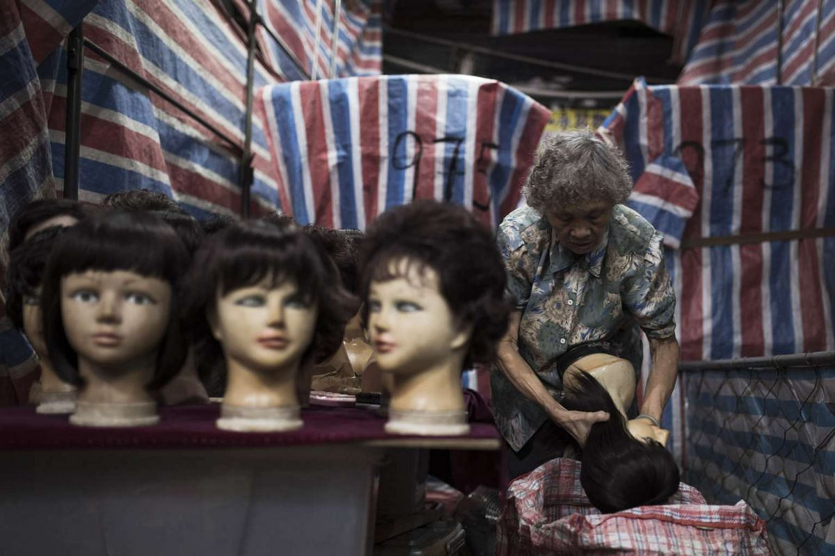 A vendor packs mannequin heads into a bag at a wig stall in a street market at night in the Mong Kok district of Hong Kong.