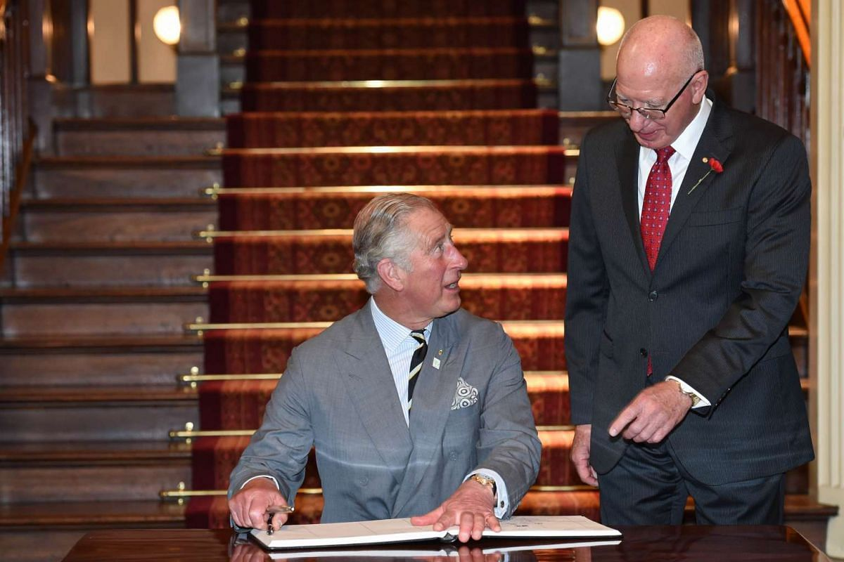 Britain's Prince Charles signs the visitors' book as Governor of New South Wales General David Hurley (right) looks on during a reception at Government House in Sydney, Australia, on Nov 12, 2015.