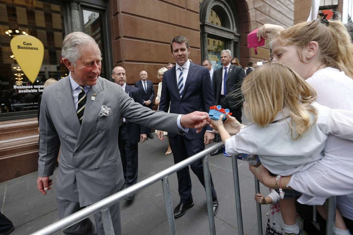Britain's Prince Charles looks at a Thomas the Tank Engine toy offered to him by one-year-old William Denezis as the prince meets well-wishers during a walk at Martin Place, in Sydney, Australia, on Nov 12, 2015.