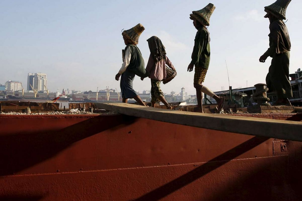 Labourers unload gravel from a boat docked in Dala township, opposite Yangon city, Myanmar.
