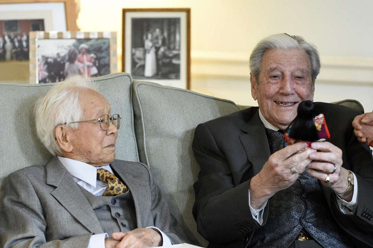 Former Sergeant from the Royal Berkshire Regiment Roy Welland (right) smiles as he receives a Kimekomi doll made by the daughter of Japanese WWII veteran Mikio Kinoshita (left).