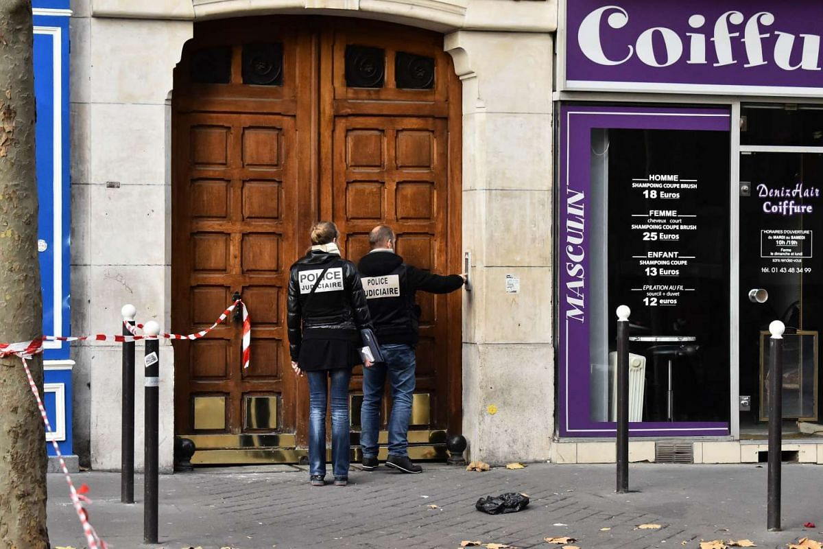Police are seen in front of a house at the Rue Faidherbe near the Rue de Charonne in Paris.