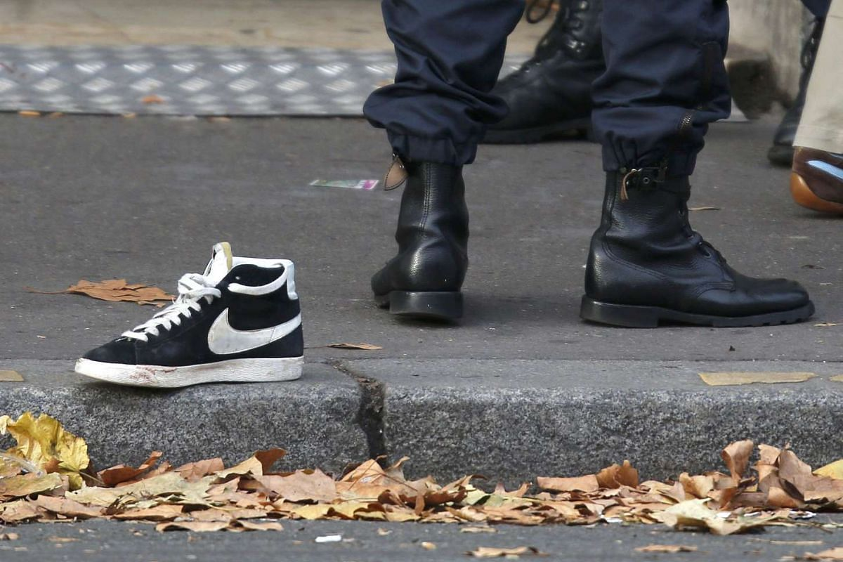 A policeman stands near an abandoned shoe that was left in the street near the Bataclan concert hall.