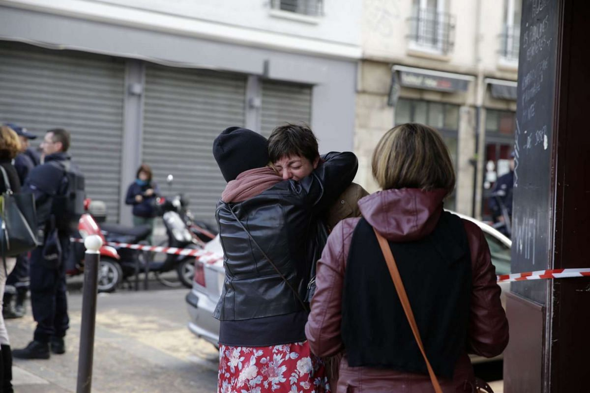 : Mourners gather outside of the Carillon bar in the 10th district of Paris.