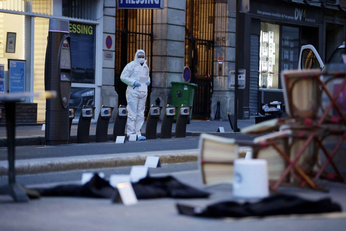 A forensic scientist inspects the scene outside of the Cafe Bonne Biere on Rue du Faubourg du Temple in Paris.