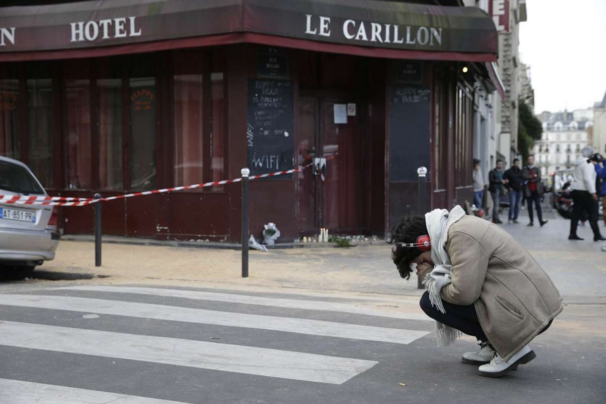 A woman mourns outside of the Carillon bar in the 10th district of Paris.