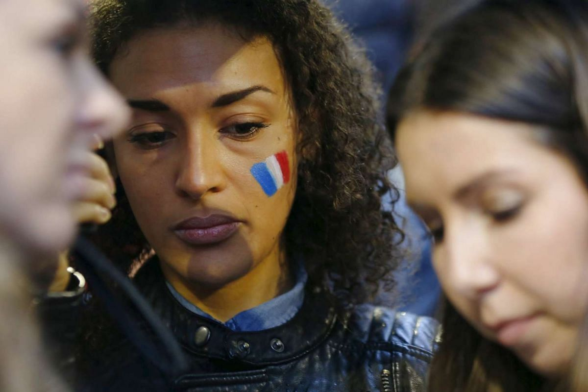 A woman wears the painted colours of France's national flag on her cheek during a candlelight vigil for the victims of the Paris attacks, in Sydney, Australia.