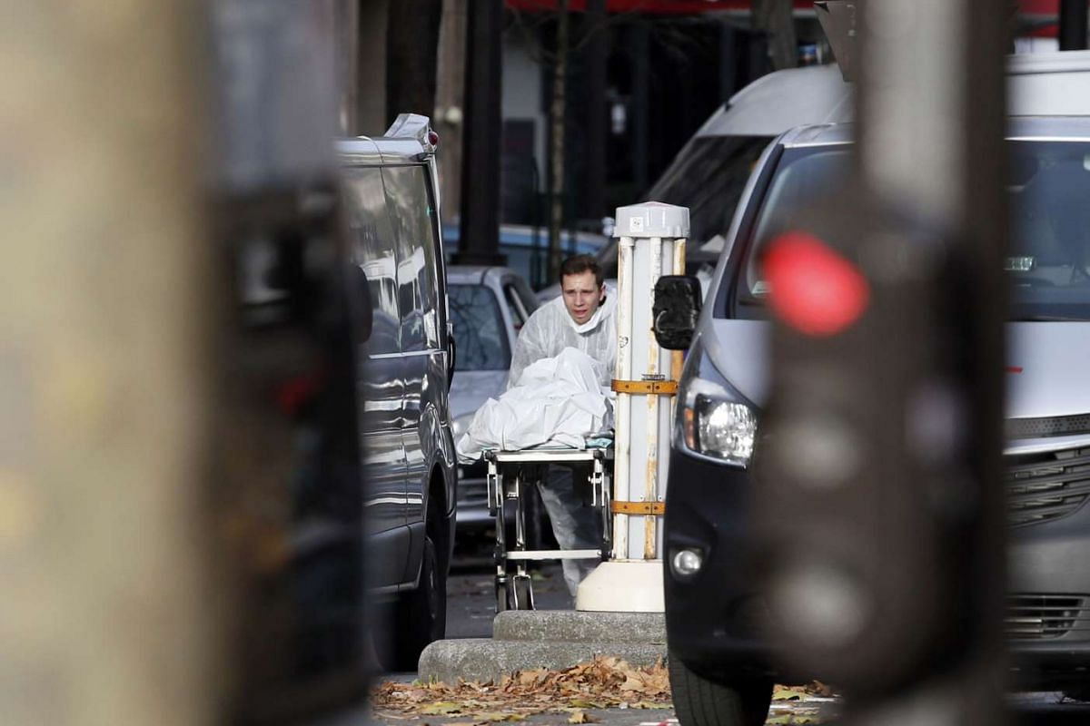 A man transports the body of a person near the Bataclan concert hall in Paris.