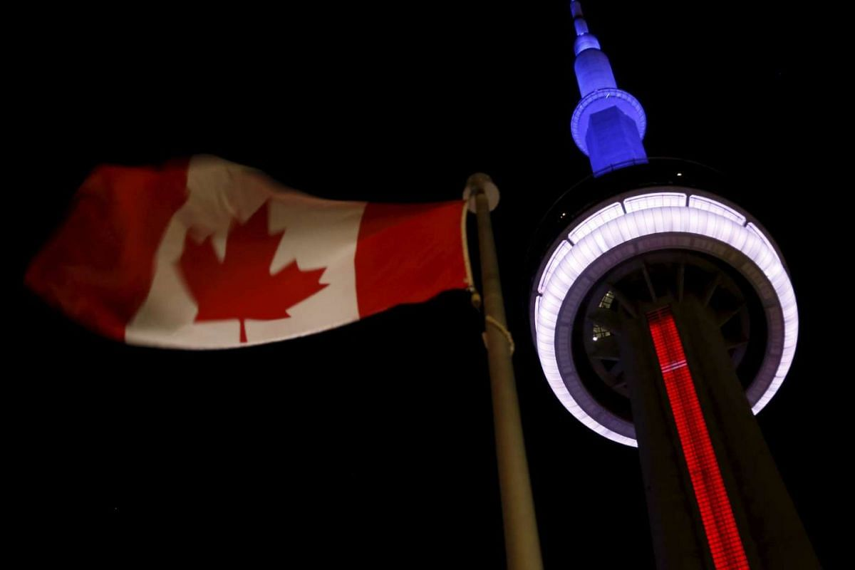 The landmark CN Tower in Toronto lit in the colours of the French flag.