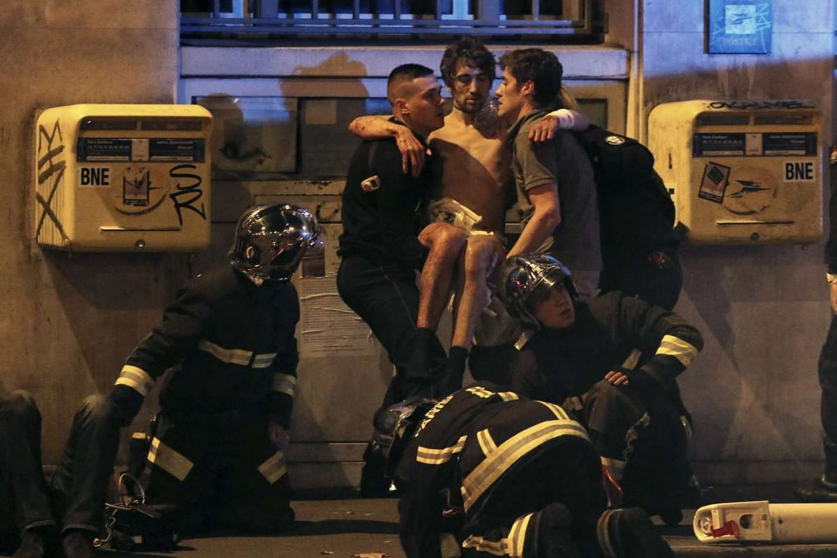 French fire brigade members aiding an injured man near the Bataclan concert hall.