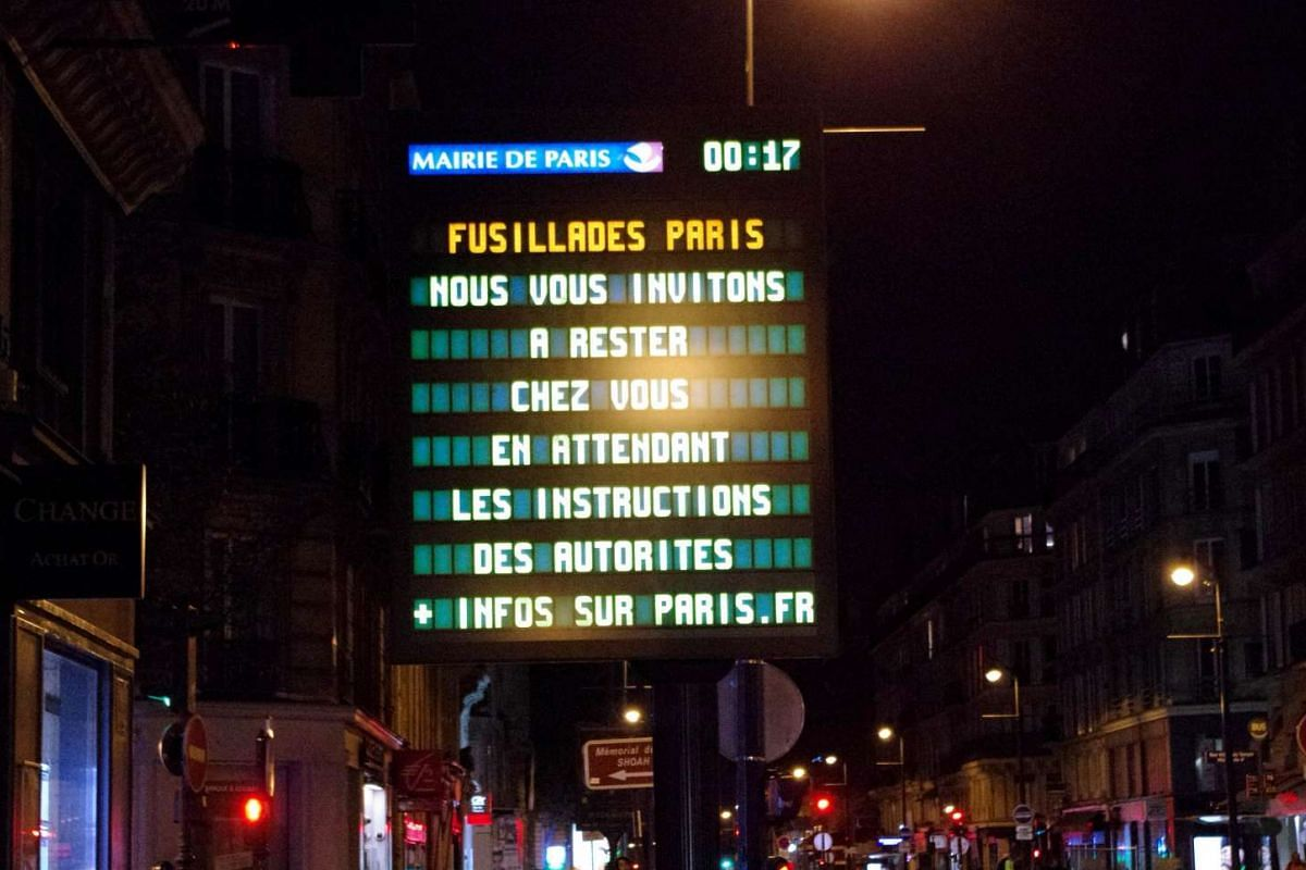 "A city advisory sign in Paris reads: ""Paris Shootings: We ask you to stay at home and await instructions from the authorities""."