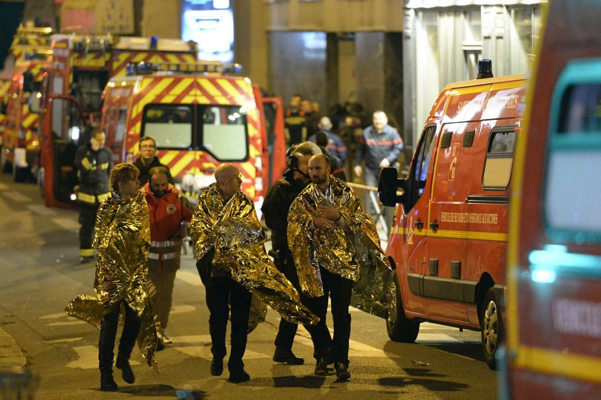 People wrapped in life emergency blankets being evacuated from the Bataclan concert hall.