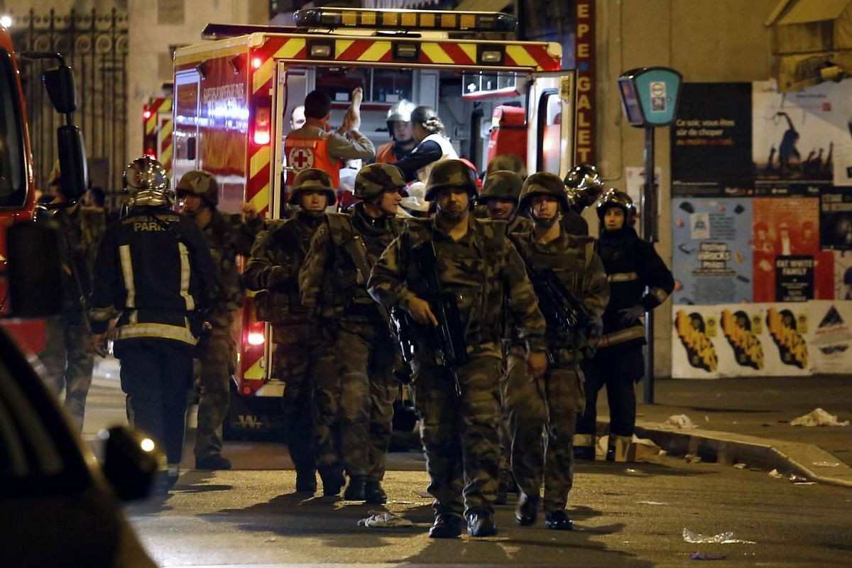Soldiers walking in front of an ambulance as rescue workers evacuate victims near La Belle Equipe in rue de Charonne.