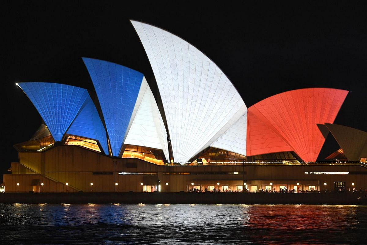 The iconic sails of the Sydney Opera House are lit in red, white and blue, resembling the colours of the French flag.
