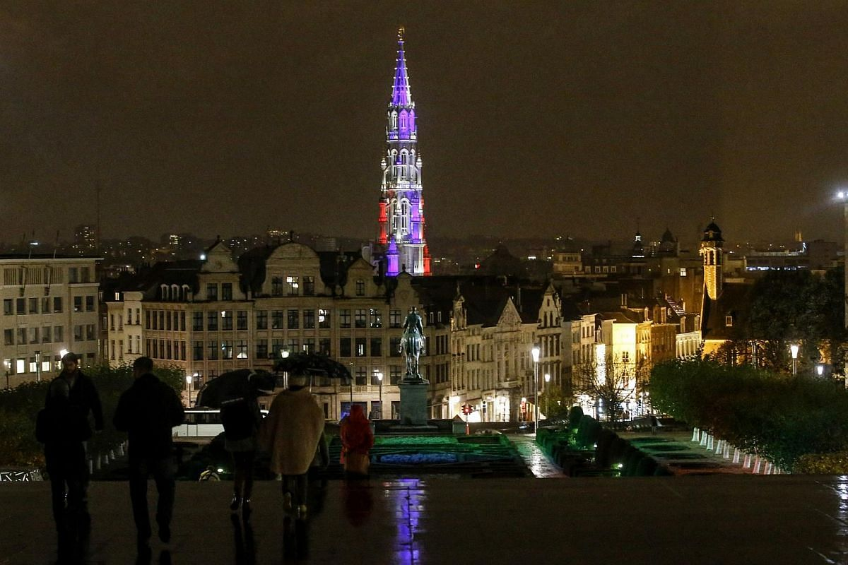 Brussels City hall tower is illuminated in the colours of the French flag, in Brussels, Belgium.